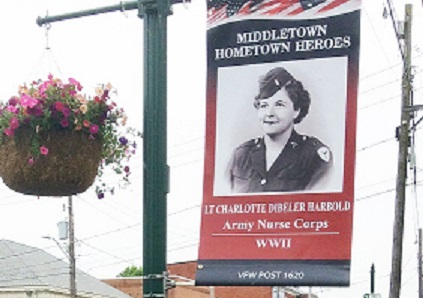 Retired Navy Captain Donald Reid stands next to a banner on South Union Street honoring an Army nurse from World War II.